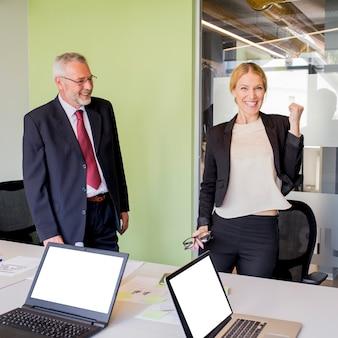 Rijpe zakenman die succesvolle gelukkige jonge onderneemster bekijkt die haar vuist dichtklemt
