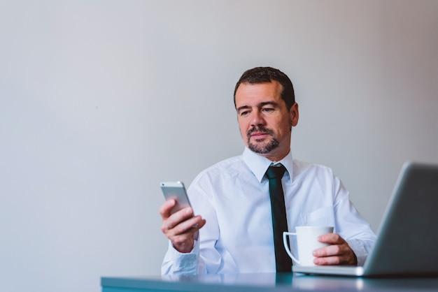 Rijpe zakenman in kostuum die celtelefoon met behulp van bij bureau in klein bureau.