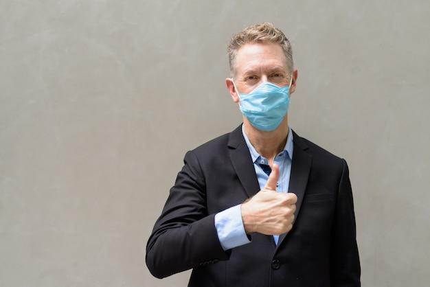 Rijpe zakenman met masker die duimen in openlucht opgeeft
