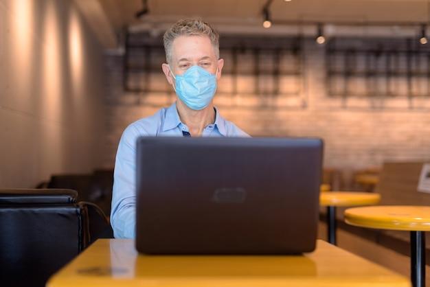 Rijpe zakenman met masker die laptop met behulp van bij de koffiewinkel