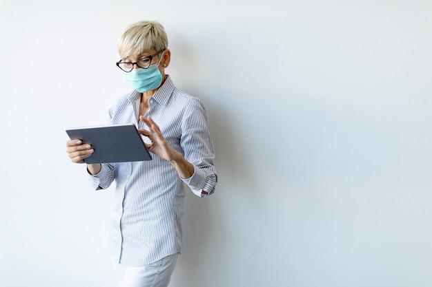 Rijpe zakenvrouw die een handheld digitale tablet gebruikt en een masker draagt om infectie door coronavirus te voorkomen