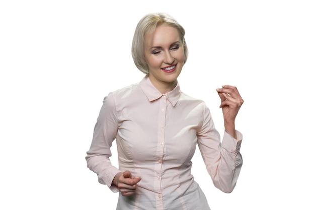 Rijpe zakenvrouw die met haar vingers knipt. portret van een schattige dame van middelbare leeftijd die een formeel overhemd draagt en van muziek geniet. geïsoleerd op wit.