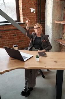 Rijpe zakenvrouw in brillen zit aan bureau met laptop en planner en papieren vliegtuigje gooien in kantoor