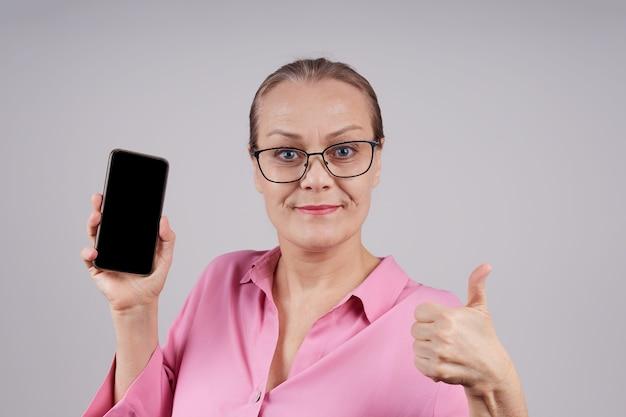Rijpe zakenvrouw in glazen, in een roze blouse, houdt een mobiele telefoon vast, toont een leeg scherm. geïsoleerde foto op grijze achtergrond met kopie ruimte.
