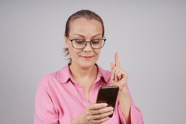 Rijpe zakenvrouw met bril, in een roze blouse, maakt gebruik van een mobiele telefoon, een bericht te typen. geïsoleerde foto op een grijze achtergrond.
