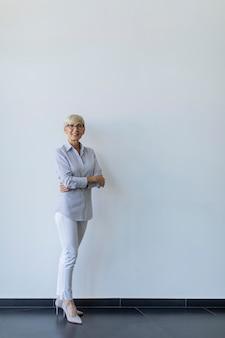 Rijpe zakenvrouw met gekruiste armen staande door de muur in het kantoor