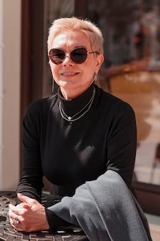 Rijpe zakenvrouw met kort kapsel draagt een zonnebril die buiten in café zit en glimlacht