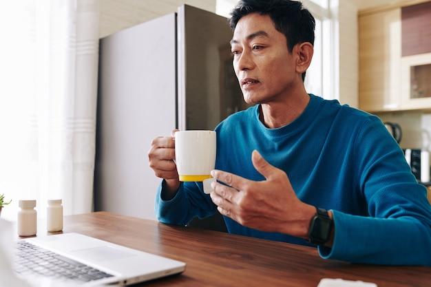 Rijpe zieke man met gelezen ogen hete thee drinken tijdens een videogesprek met arts of collega