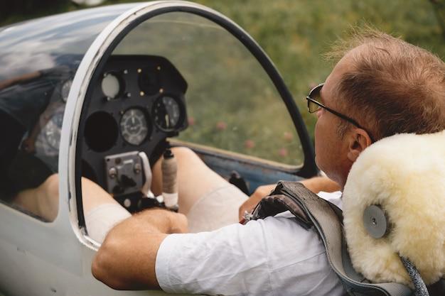 Rijpe zweefvliegtuigpiloot in het vliegtuig voor vlucht in vliegtuig met vaste vleugels