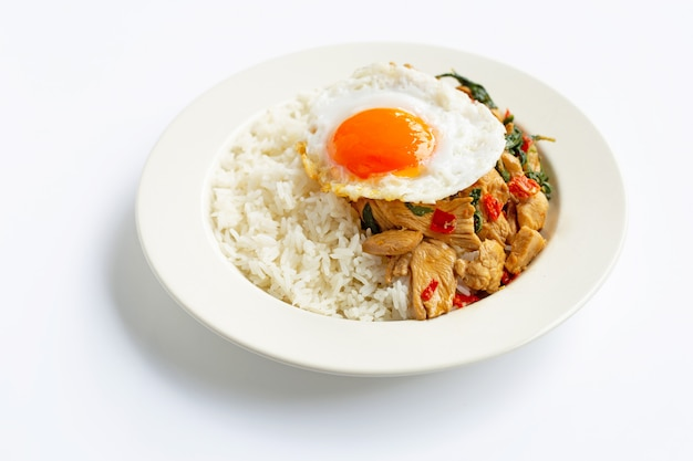 Rijst afgedekt met geroerbakte kip en heilige basilicum, gebakken ei