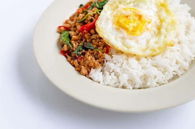 Rijst afgedekt met geroerbakte varkensvlees met basilicum en gebakken ei