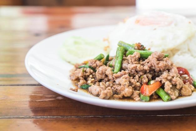 Rijst bedekt met roergebakken gefrituurd varkensvlees en basilicum