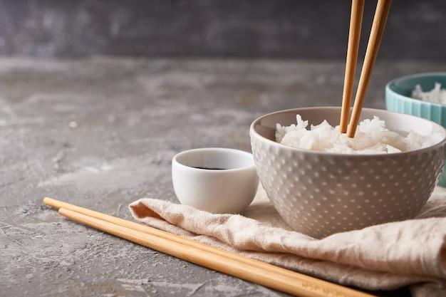 Rijst eetstokjes, over een kom witte rijst, sojasaus op een donkergrijze achtergrond kopieer de ruimte