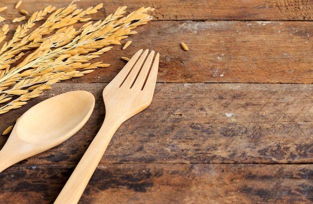 Rijst en houten lepel en vork op houten lijst