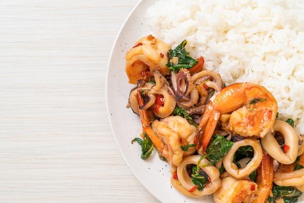 Rijst en roergebakken zeevruchten (garnalen en inktvis) met thaise basilicum. aziatische eetstijl
