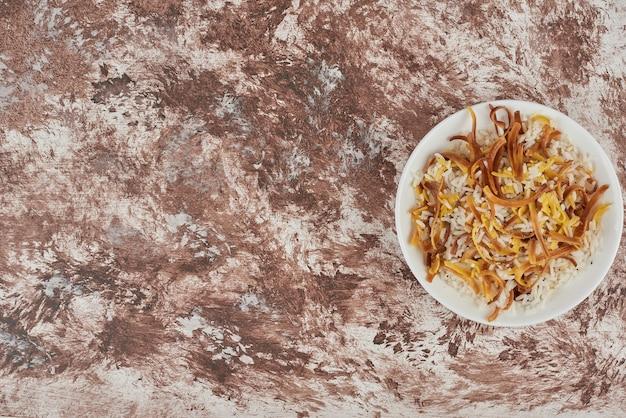 Rijst garnituur en noedels in een witte plaat.