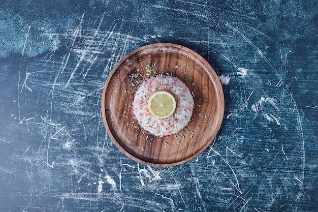 Rijst garnituur met citroen in een houten schotel, bovenaanzicht.