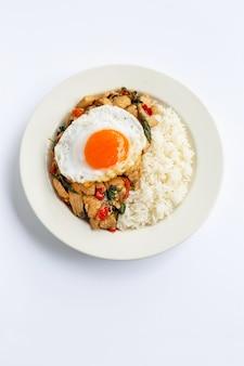 Rijst gegarneerd met gewokte kip en heilige basilicum, gebakken ei