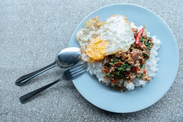 Rijst gegarneerd met gewokte varkensgehakt en basilicum met gebakken ei.