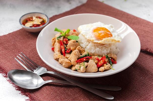 Rijst gegarneerd met roergebakken basilicum met kip en een gebakken ei op een witte plaat op bruin tafelkleed met vissaus thais straatvoedsel