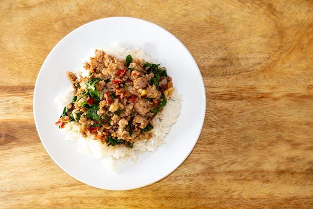Rijst gegarneerd met roergebakken varkensvlees en basilicum in een witte plaat op een houten tafel met ruimte om tekst te zetten.