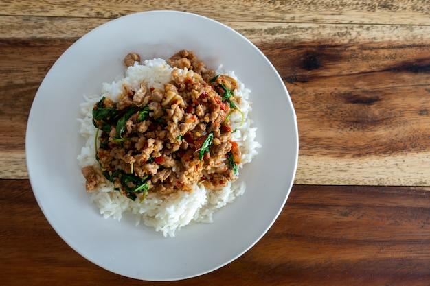 Rijst gegarneerd met roergebakken varkensvlees en basilicum in witte schotel op houten tafel.