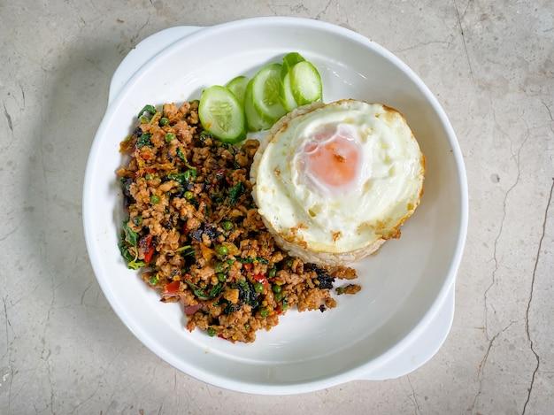 Rijst gegarneerd met roergebakken varkensvlees en basilicum met een gebakken ei op tafel