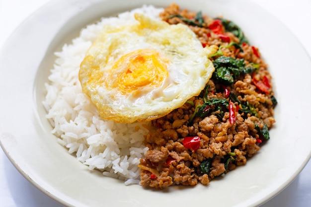 Rijst gegarneerd met roergebakken varkensvlees met basilicum en gebakken ei