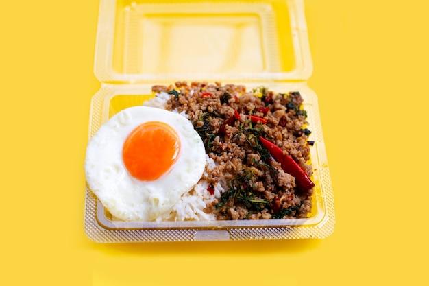 Rijst gegarneerd met roergebakken varkensvlees met heilige basilicum en gebakken ei in plastic voedselcontainer op gele achtergrond.