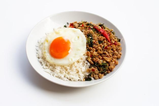 Rijst gegarneerd met roergebakken varkensvlees met heilige basilicum en gebakken ei op witte achtergrond.