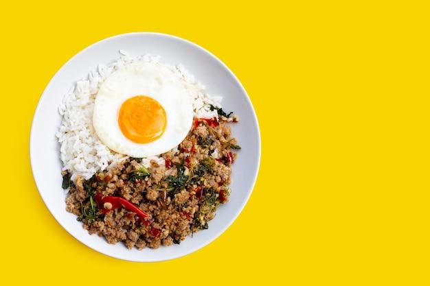 Rijst gegarneerd met roergebakken varkensvlees met heilige basilicum en gebakken ei