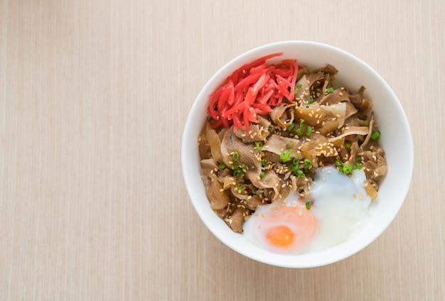 Rijst gegarneerd met varkensvlees en onsenier