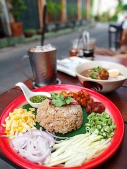 Rijst gemengd met garnalenpasta op een houten tafel