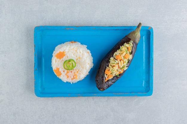 Rijst in aubergine naast rijst op het bord, op het marmer.