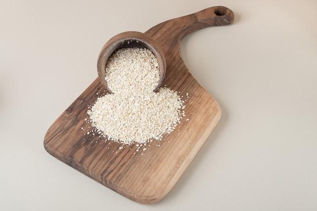 Rijst in een houten kop op een houten schotel.