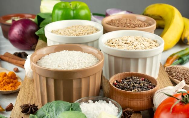 Rijst in een kom close-up op de achtergrond verschillende granen en groenten. gezond eten lekker eten. vegetarisch eten. culinaire achtergrond voor recepten. voedsel achtergrond.