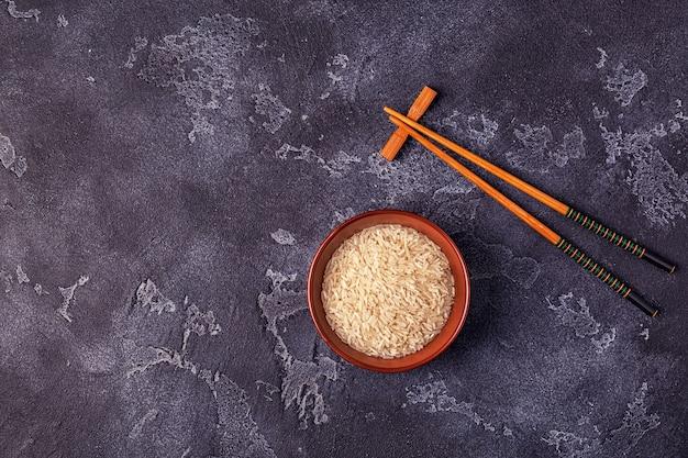 Rijst in een kom en houten eetstokjes
