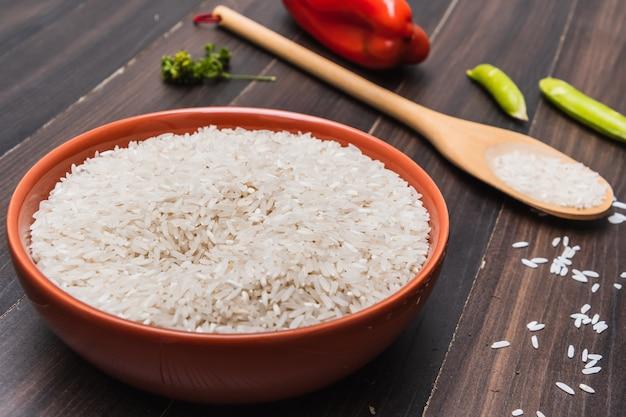 Rijst in een kom, groenten en houten lepel op een bruin houten oppervlak