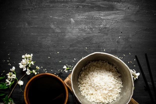 Rijst in een oude pan en sojasaus. op een zwarte houten achtergrond.