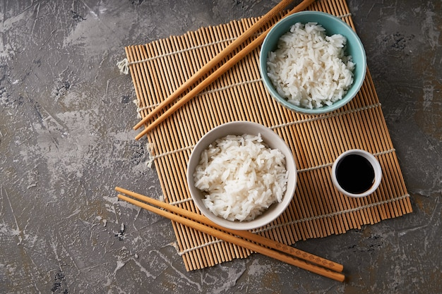 Rijst in een porseleinen kom, met japanse eetstokjes, sojasaus, geserveerd op een grijze stenen tafel kopieer ruimte bovenaanzicht