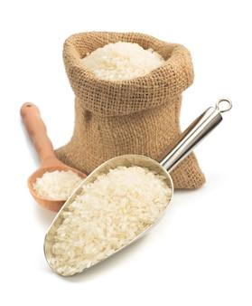 Rijst in lepel op wit wordt geïsoleerd dat