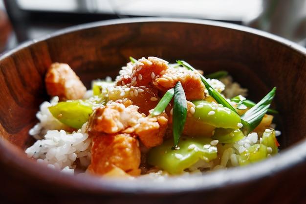Rijst in saus met roergebakken groenten, ananas en zalm in houten kom