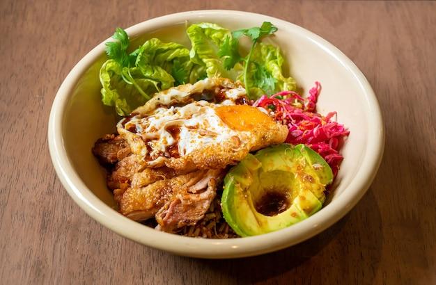 Rijst met gebakken kip teriyaki saus en avocado en gebakken ei - fusion food