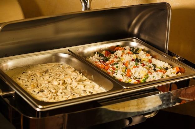 Rijst met groenten en champignons in een romige saus in het hotel op het dienblad met voedsel, voeding, seminarie, koffiepauzes, ontbijt, lunch, diner, buffet. gezond en smakelijk eten