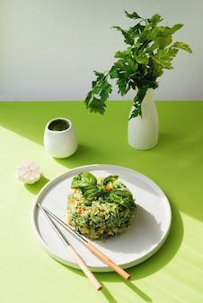 Rijst met groenten en pestosaus, creatief beeld van een aziatisch gerecht met fel zonlicht