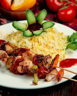 Rijst met kip en groenten op een stokje