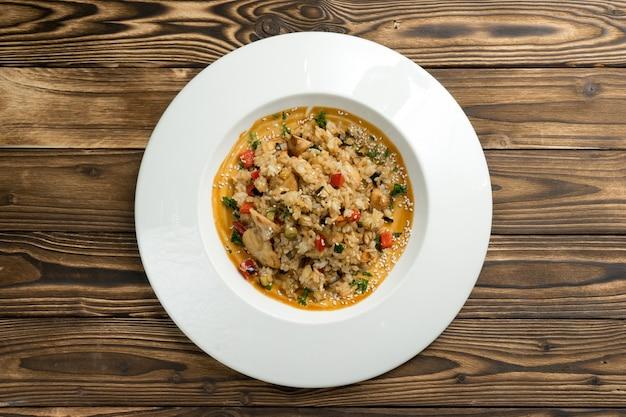 Rijst met kipfilet, rode peper en andere groenten in zoetzure saus, bestrooid met sesamzaadjes. Premium Foto