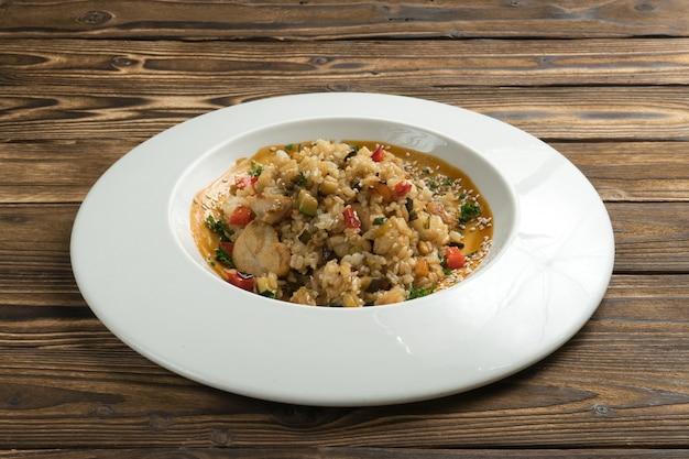 Rijst met kipfilet, rode peper en andere groenten in zoetzure saus, bestrooid met sesamzaadjes.