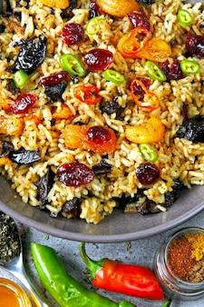 Rijst met kruiden en gedroogde vruchten. veganistische kom met pikante rijst.