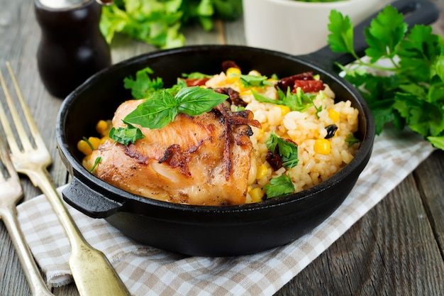 Rijst met mais, sojasaus en gebakken kippendij op een gietijzeren koekenpan